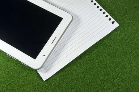 Tablet and line blank papers on green grass photo