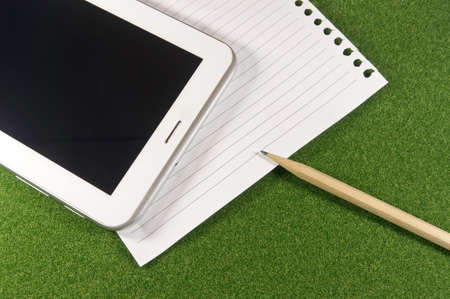 Digital tablet with white paper and pencil on green grass photo