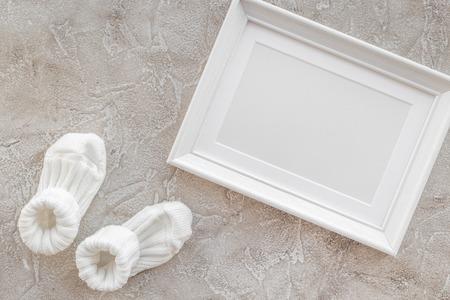 Thema voor moderne babydouche met kindschoenen en wit kader op grijze steen achtergrond hoogste meningsruimte voor tekst Stockfoto - 78692213