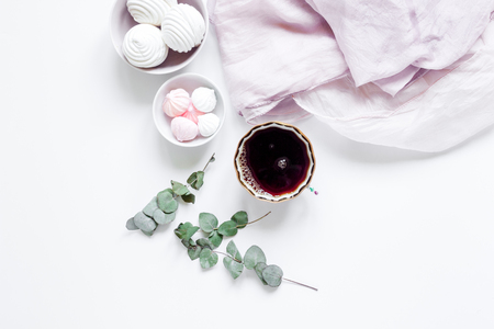 woman lunch with marsh-mallow, cup of coffee and flowers trendy design in soft light on white table background flat lay