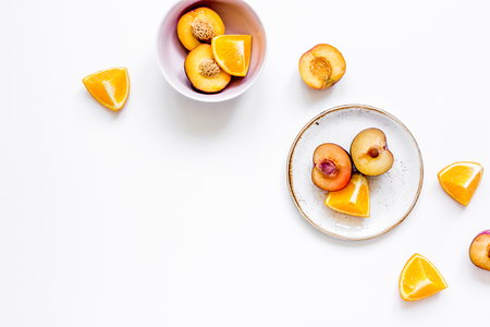 breackfast: woman summer breackfast with orange and peach fruits on white desk background flat lay mockup Stock Photo