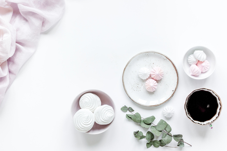 woman lunch with marsh-mallow, cup of coffee and flowers trendy design in soft light on white table background flat lay v Stock Photo