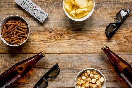 ビールと木製の背景上面にリモート コントロールのモックアップをチップを搭載したテレビを見て、