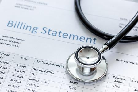 medical treatmant billing statement with stethoscope on stone desk background