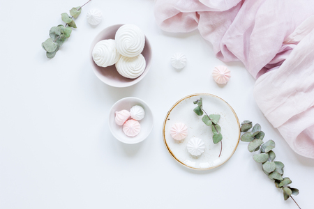 woman lunch with marsh-mallow in plate and flowers soft light on white table background flat lay Stock Photo
