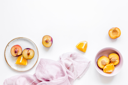 tropical fruits design with orange and peach on fabric white table background top view mock up