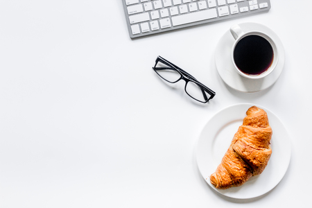 glazen, croissant en kopje koffie op bureau voor zakelijke ontbijt op het werk witte achtergrond bovenaanzicht mock-up