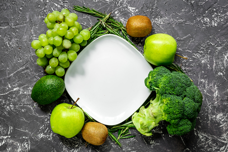 breackfast: green fresh vegetables and fruits for healthy salad on dark kitchen table background top view Stock Photo