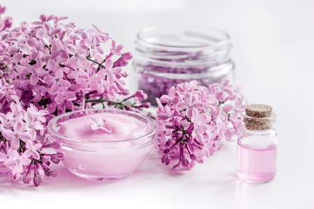 take bath with lilac cosmetic spa set and blossom on white table background