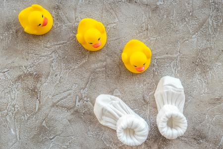 babyspeelgoed en schoenen voor baby showerontwerp op grijze hoogste mening als achtergrond Stockfoto