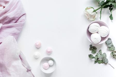zoete marsh-mallow en lente bloemen op vrouw witte bureau achtergrond bovenaanzicht mockup Stockfoto