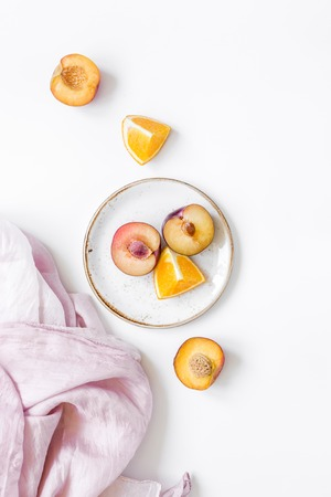 tropical fruits design with sliced orange and peach on fabric on white table background top view Stock Photo