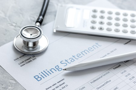 health care billing statement with doctors stethoscope on stone background