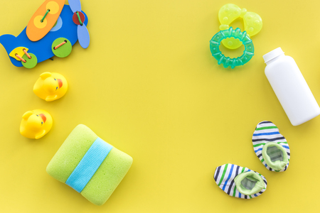 Babyverzorgingstoebehoren, speelgoed en kleding op gele achtergrond hoogste meningsspot omhoog Stockfoto