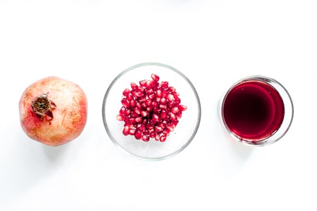 summer dessert with red juice and cut pomegranate on white background top view