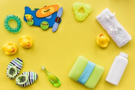 La cura del bambino con l'insieme del cosmetico del bagno, gli anatroccoli e l'asciugamano sul modello giallo osservano il modello di vista superiore Archivio Fotografico - 79313275