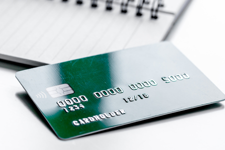 work place with business credit cards on notebook for payment on white office desk background close up