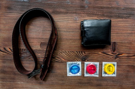 Condoms in package, wallet and belt on wooden background top view