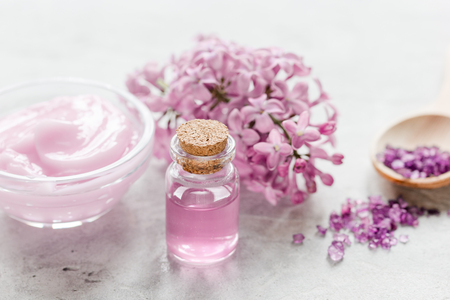 homemade organic salt, cream, extract in lilac cosmetic set with flowers on stone table background