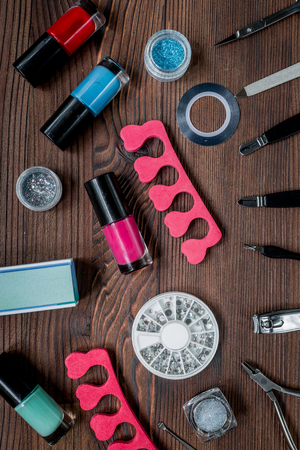 manicure preparation set with nail polish bottles on wooden table background top view
