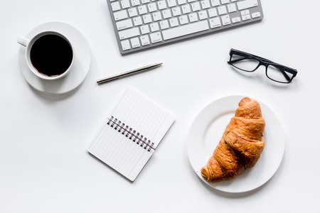 coffee and croissant for breakfast of businessman on white office desk background top view space for text Reklamní fotografie