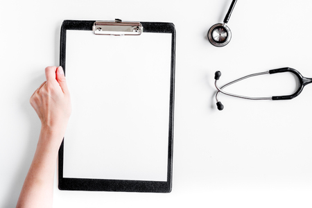 doctors work desk in hospital with notepad and stethoscope white background top view mockup Imagens