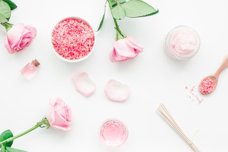 body treatment with rose flowers and cosmetic set on white desk background top view Stock Photo