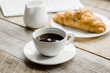 コーヒーと木製オフィス デスク背景にビジネスマンの朝食のクロワッサン 写真素材