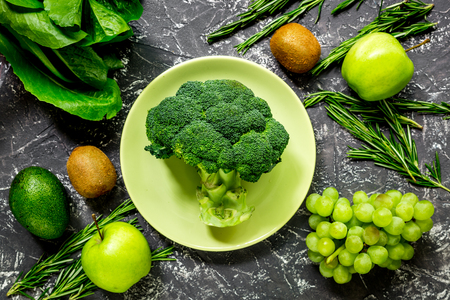 breackfast: organic food for homemade salad with green vegetables on dark desk background top view