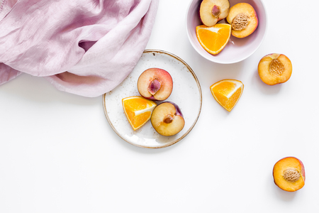 woman summer breackfast with orange and peach fruits and fabric on white background flat lay mockup Stock Photo