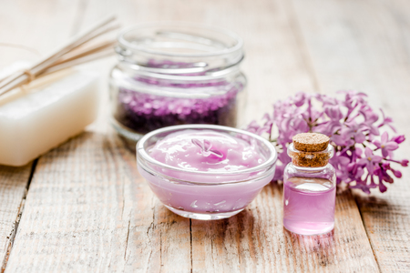 lilac natural cosmetic set for spa with salt wooden table background