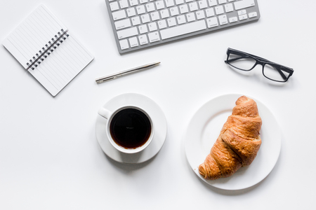 Office lunch with coffee and croissant, noteook on white table background top view space for text