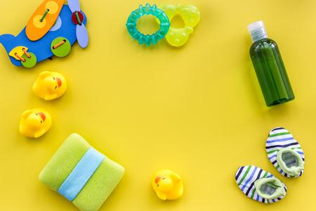 Accesorios para el cuidado del bebé, juguetes y ropa en la vista superior del fondo de la mesa amarilla simulacro