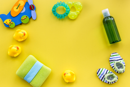 Baby care accessories, toys and clothing on yellow table background top view mock up