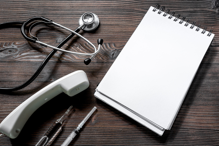 phonendoscope, syringe, ampoule and notebook on dark wooden desk top view call doctor. Stock Photo