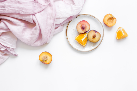 napkin, cut peach and orange for exotic fruit on white table background top view mockup Stock Photo