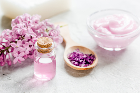 woman bath: take bath with lilac cosmetic set and blossom on stone table background Stock Photo