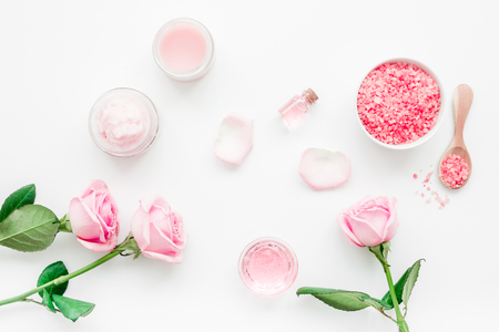 rose organic cosmetics with sea salt, cream and oil on white table background top view mock up