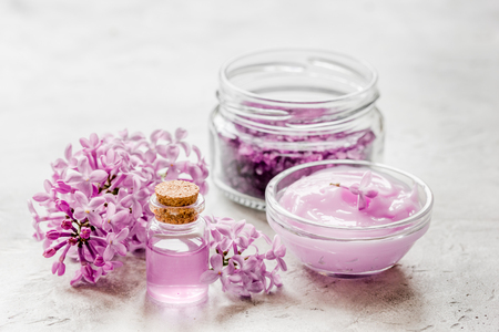 take bath with lilac cosmetic spa set and blossom on stone table background Stock Photo