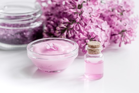 lilac cosmetics with flowers and homemade spa set on white table background