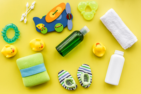 bath cosmetic set for kids, towel and baby toys on yellow background top view pattern Foto de archivo