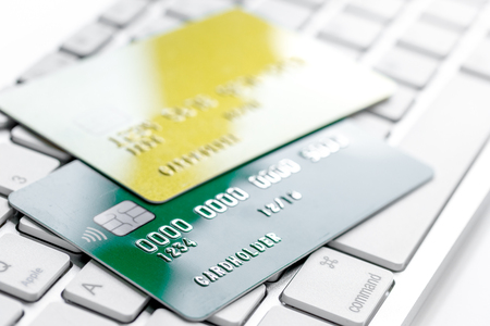 credit cards for business payments on keyboard for work on white office desk background close up