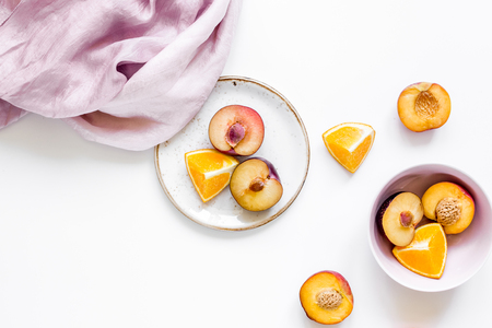 tropical peach and orange fruits for fresh summer juice with towel on white table background top view space for text Stock Photo