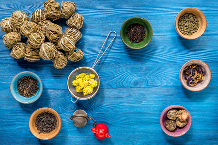 Different kinds of herbal tea on blue wooden table top view