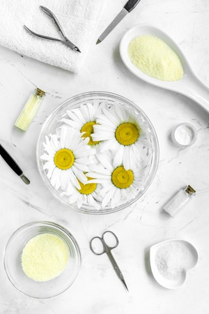 natural cosmetics with bowl of chamomiles and tools for manicure on white textural background top view