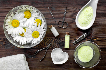 Spa composition on dark wooden desk with chamomile, towel and manicure set top view. Stock Photo