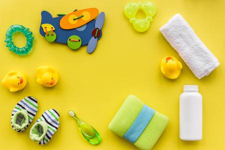 Los accesorios, los juguetes y la ropa del cuidado del bebé en la opinión superior del fondo amarillo de la tabla imitan para arriba Foto de archivo - 80159357