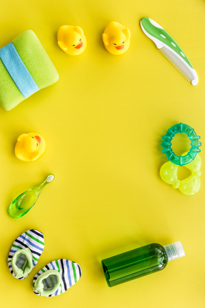 cosmetics for baby bath taking, towel and toys on yellow background top view space for text Stock Photo