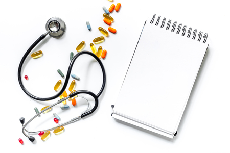 Medical things with notebook on white background top view composition with phonendoscope and drugs. Stock fotó - 80159752