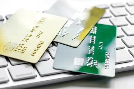 zaken met creditcards voor betaling op toetsenbord op bureau witte achtergrond dicht omhoog